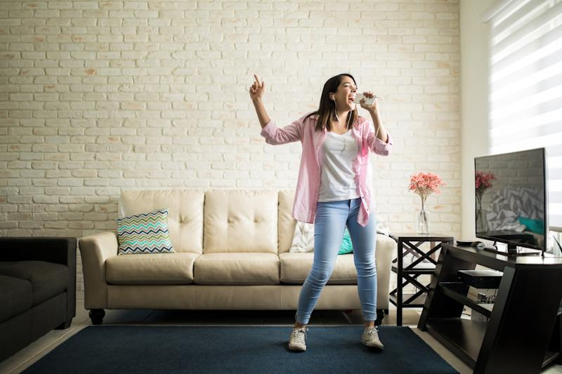A young woman sings karaoke into her smartphone in her living room.