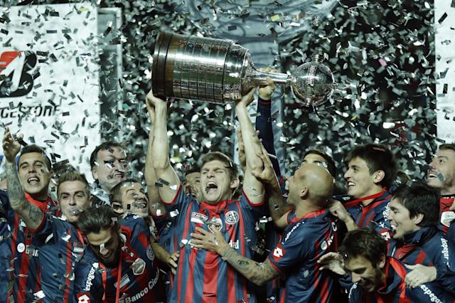 Walter Kannemann of Argentina's San Lorenzo, center, lifts the trophy after winning the 2014 Copa Libertadores championship against Paraguay's Nacional during the Copa Libertadores final soccer match in Buenos Aires, Argentina, Wednesday, Aug. 13, 2014. (AP Photo/Victor R. Caivano)