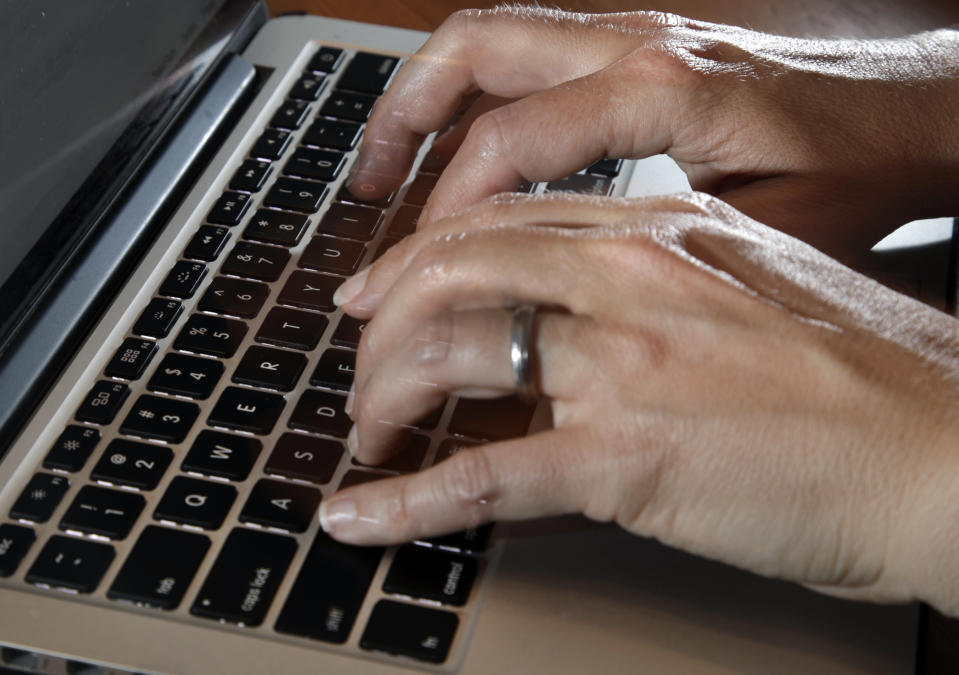 In this Monday, June 19, 2017, photo, a person types on a laptop keyboard, in North Andover, Mass. One of the nation's biggest telemedicine providers is spending more than $18 billion to stoke an approach to care that grew explosively during the pandemic. Teladoc Health plans to dive deep into managing the health of patients with diabetes and high blood pressure with a cash-and-stock deal for Livongo Health. Telemedicine involves care delivered remotely, often with a live video connection through patient smartphones or tablets. (AP Photo/Elise Amendola)