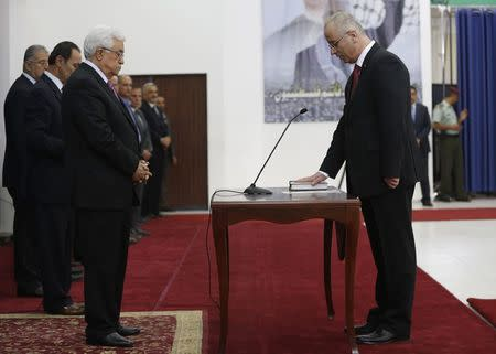 Palestinian Prime Minister Hamdallah stands in front of Palestinian President Abbas during a swearing-in ceremony of the unity government, in the West Bank city of Ramallah