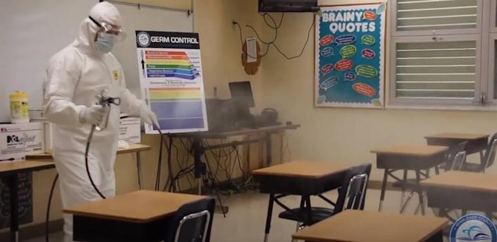 To limit the potential spread of COVID-19 in Miami-Dade County Public Schools, the district imposed various health-safety measures, such as enhanced cleaning of schools and buses. A screen grab of a district video shows a worker disinfecting a classroom.