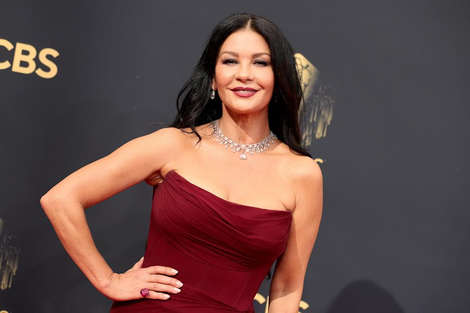 Catherine Zeta Jones wears wine coloured strapless dress and diamond necklace on the 2021 Emmys red carpet.