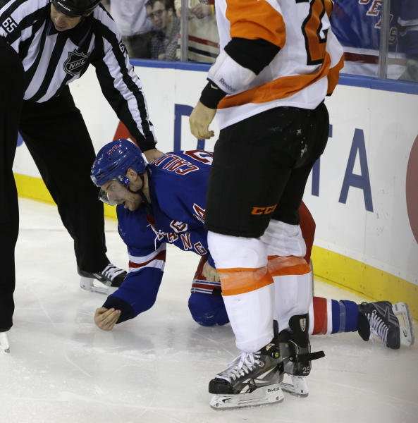Linesman Pierre Racicot (65) holds New York Rangers right wing Ryan Callahan (24) after Callahan was injured in a fight with Philadelphia Flyers center Maxime Talbot (25) of Cananda in the third period of their NHL hockey game at Madison Square Garden in New York, Tuesday, Jan. 29, 2013. The Rangers defeated the Flyers 2-1. Callahan didn't return to the game. (AP Photo/Kathy Willens)