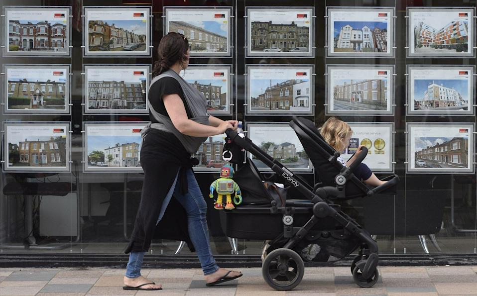 A woman looks at adverts in an property agent's window in southwest London. Average house price reached an all-time high in December, while affordability worsened. Photo: EPA-EFE