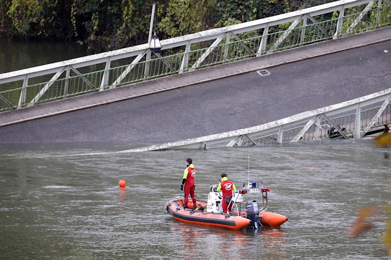 Picture of rescuers on a boat, working to recover victims after a suspension bridge collapsed over the Tarn river in Mirepoix-sur-Tarn, near Toulouse, southern France.