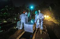 Gravediggers bury a Covid-19 coronavirus victim at a cemetery in Bogor, on the outskirts of Jakarta, Indonesia on March 2, 2021