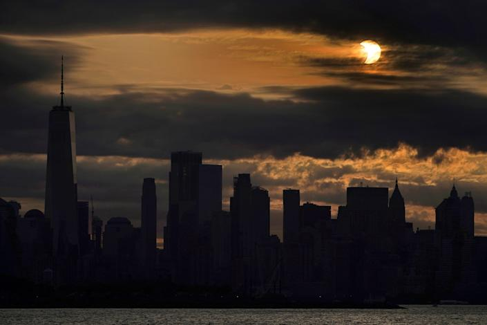 The sun is partially eclipsed as it rises over lower Manhattan in New York, Thursday, June 10, 2021.