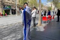 A man covered in an Israeli flag stands still as a two-minute siren marking the annual Israeli Holocaust Remembrance Day is heard in Jerusalem