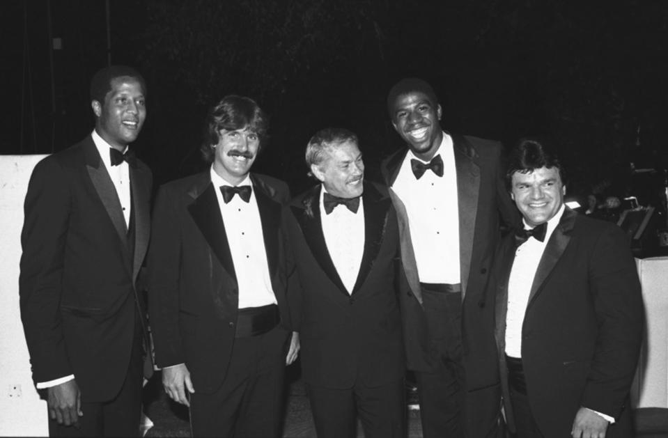 FILE - In this June 18, 1980 file photo, Jerry Buss, center, poses with players from his teams at a charity event in Beverly Hills, Calif. From left are Los Angeles Lakers' Jamaal Wilkes, Los Angeles Kings' Charlie Simmer, Buss, Lakers' Magic Johnson and Kings' Marcel Dionne. Buss, the Lakers' playboy owner who shepherded the NBA franchise to 10 championships, has died. He was 80. Bob Steiner, an assistant to Buss, confirmed Monday, Feb. 18, 2013 that Buss had died in Los Angeles. Further details were not available. (AP Photo/Reed Saxon, File)