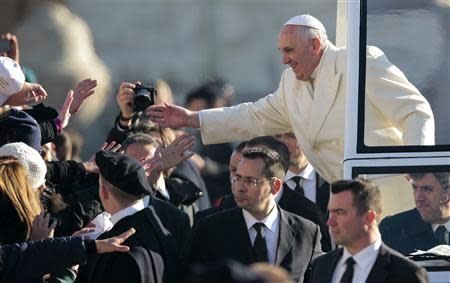 Pope Francis gives blessings as he arrives to lead his Wednesday general audience in Saint Peter's square at the Vatican December 18, 2013. REUTERS/Tony Gentile