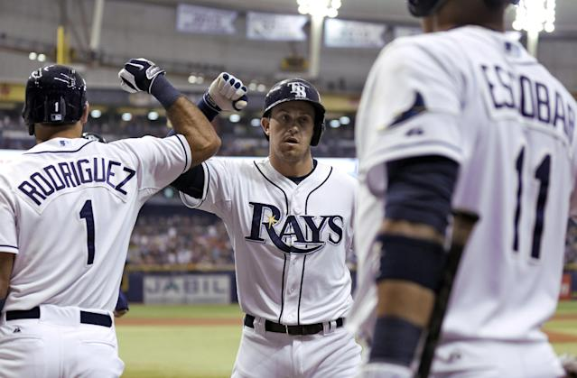 Tampa Bay Rays' Evan Longoria, center, high fives teammates Sean Rodriguez, left, and Yunel Escobar after his home run off Los Angeles Angels starting pitcher C.J. Wilson during the first inning of a baseball game Saturday, Aug. 2, 2014, in St. Petersburg, Fla. Rays' Brandon Guyer also scored on the home run. (AP Photo/Chris O'Meara)