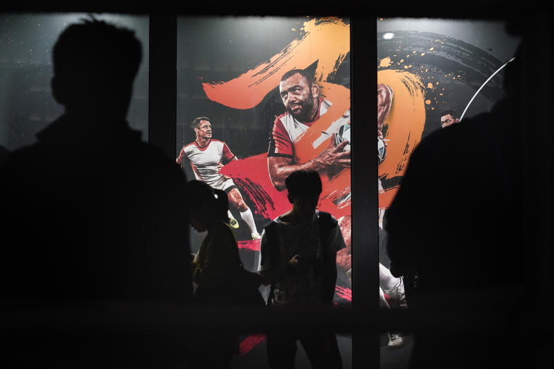 People are silhouetted against an advertisement showing an image of Japan captain Michael Leitch outside an official merchandise store of the Rugby World Cup Wednesday, Sept. 18, 2019, in Tokyo. (AP Photo/Jae C. Hong)