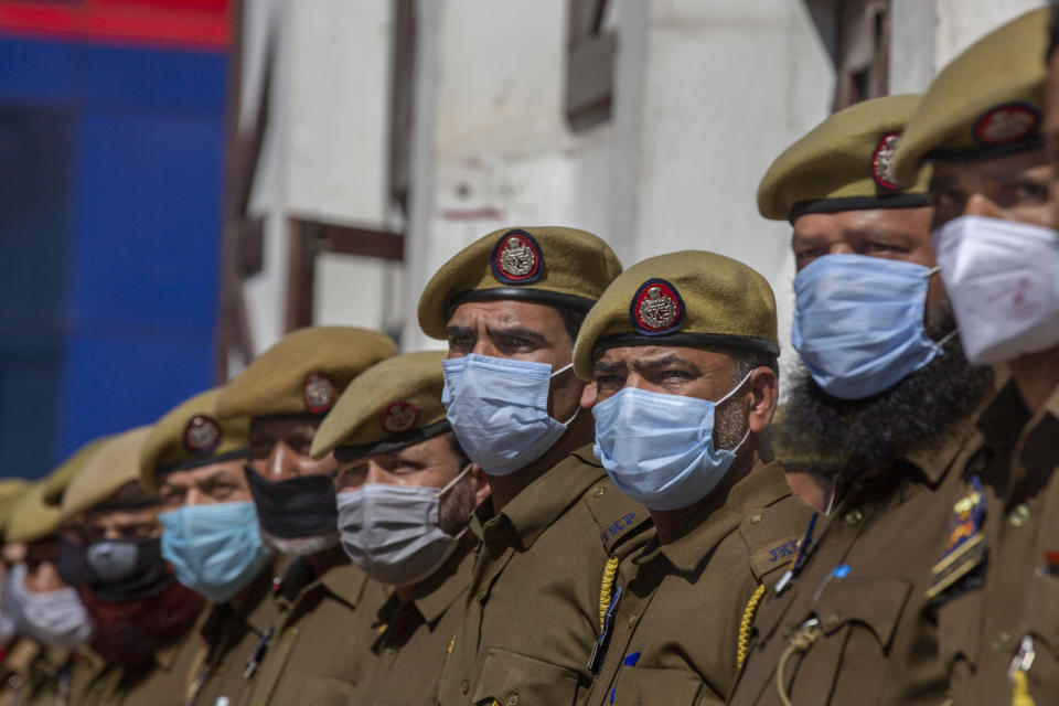 Indian police officer attends the wreath laying ceremony of their colleague Rameez Ahmad who was killed in an attack in Srinagar, Indian controlled Kashmir, Thursday, April 1, 2021. Gunmen in disputed Kashmir on Thursday killed a policeman as they tried to storm the residence of a politician of India's ruling party, police said. (AP Photo/ Dar Yasin)