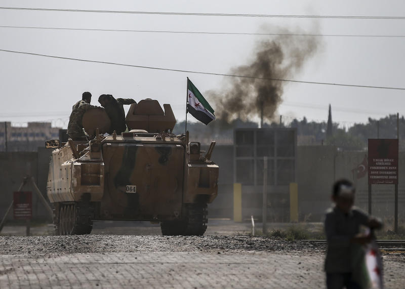 Turkish-backed Syrian opposition fighters on an armoured personnel carrier drive to cross the border into Syria, in Akcakale, Sanliurfa province, southeastern Turkey, Friday, Oct. 18, 2019. Fighting continued in a northeast Syrian border town at the center of the fight between Turkey and Kurdish forces early Friday, despite a U.S.-brokered cease-fire that went into effect overnight. (AP Photo/Emrah Gurel)