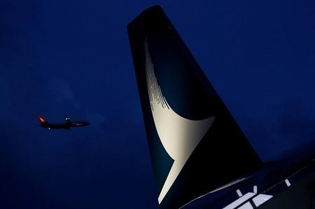 FILE PHOTO: Plane flies behind a new Cathay Pacific Airways Airbus A350 after being received by the airline at Hong Kong