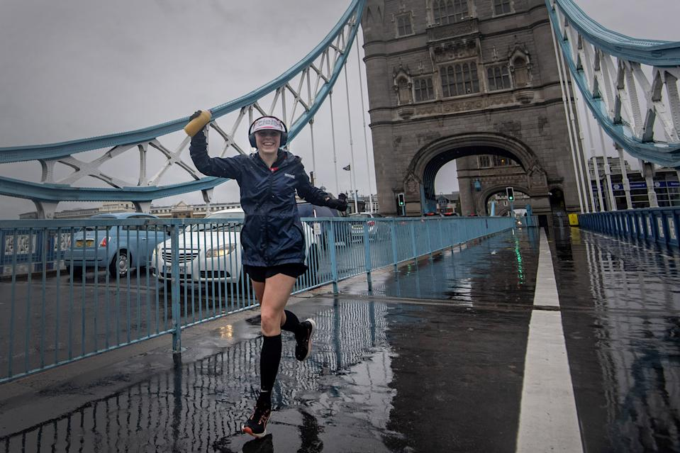 A runner wearing a London Marathon running number crosses Tower Bridge as some 45,000 people are running or walking the 40th London Marathon along their own 26.2-mile route around the UK, after the event originally planned for April 26 was postponed due to coronavirus. (Photo by Victoria Jones/PA Images via Getty Images)