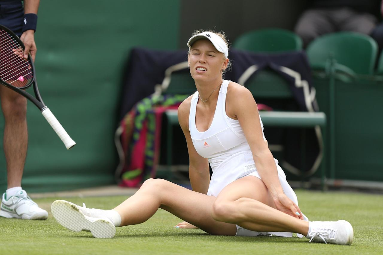 Denmark's Caroline Wozniacki holds her ankle after slipping during her match against Czech Republic's Petra Cetkovska during day three of the Wimbledon Championships at The All England Lawn Tennis and Croquet Club, Wimbledon.