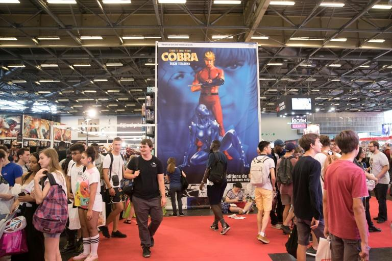 Visitors walk past a large poster for manga comic series 'Cobra the Space Pirate' by Buichi Terasawa at the 2018 Japan Expo exhibition on July 5, 2018 in Villepinte, near Paris