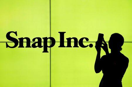 FILE PHOTO - A woman stands in front of the logo of Snap Inc. on the floor of the New York Stock Exchange in New York City
