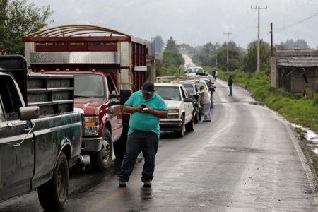 A driver checks his phone as members of the Supreme Indigenous Council block the entry to their community to avoid the installation of polling stations for Mexico's general election in the indigenous Purepecha town of Zirahuen, in Michoacan state, Mexico June 28, 2018. Picture taken June 28, 2018. REUTERS/Alan Ortega