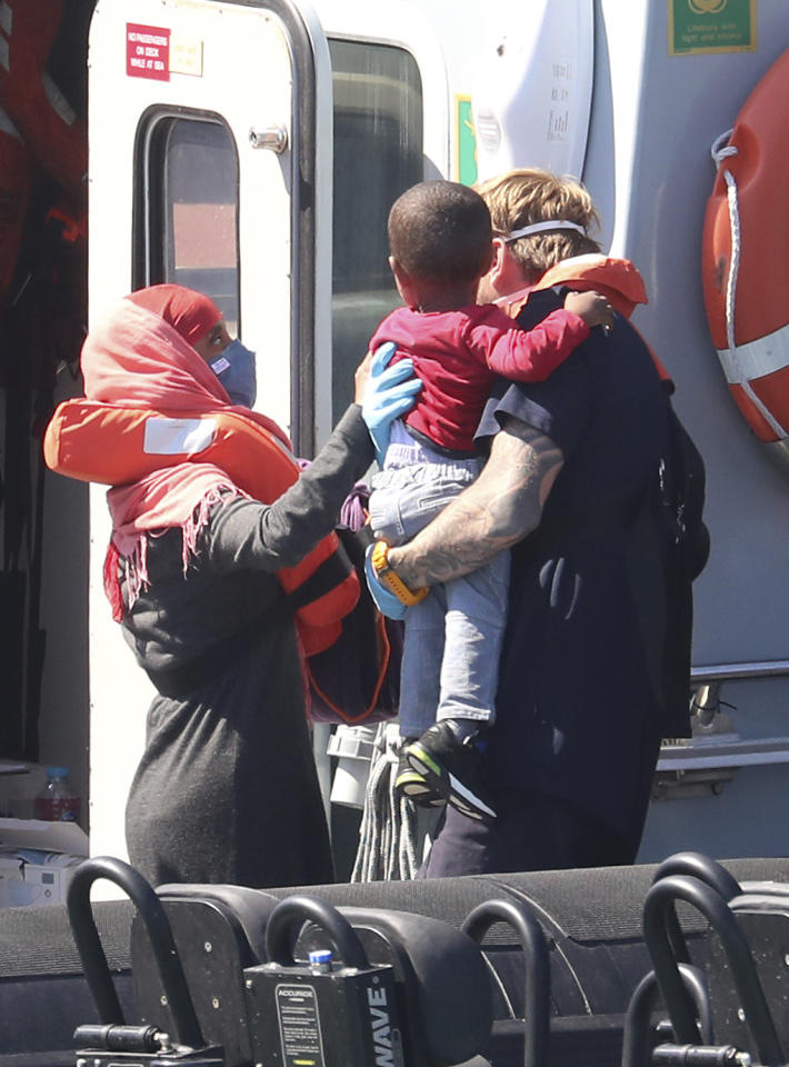 A Border Force officer helps a child from a Border Force vessel as a group of people thought to be migrants are brought into the port city of Dover, England, from small boats, Friday Aug. 7, 2020. The British government says it will strengthen border measures as calm summer weather has prompted a record number of people to attempt the risky sea crossing in small vessels, from northern France to England. (Gareth Fuller/PA via AP)