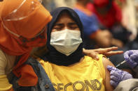 A woman reacts as she receives a shot of Sinovac's COVID-19 vaccine during a mass vaccination for traders and workers at a shopping mall in Tangerang, Indonesia, Monday, March 1, 2021. (AP Photo/Tatan Syuflana)
