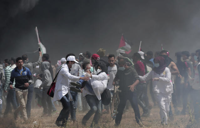 <p>Palestinian medics evacuate a wounded colleague during clashes with Israeli troops along Gaza's border with Israel, east of Khan Younis, Friday, April 6, 2018. (Photo: Adel Hana/AP) </p>