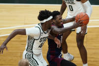 Detroit Mercy guard Antoine Davis drives to the basket as Michigan State forward Gabe Brown (44) defends during the second half of an NCAA college basketball game Friday, Dec. 4, 2020, in East Lansing, Mich. (AP Photo/Carlos Osorio)