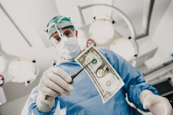 A surgeon clamping a one dollar bill with forceps.