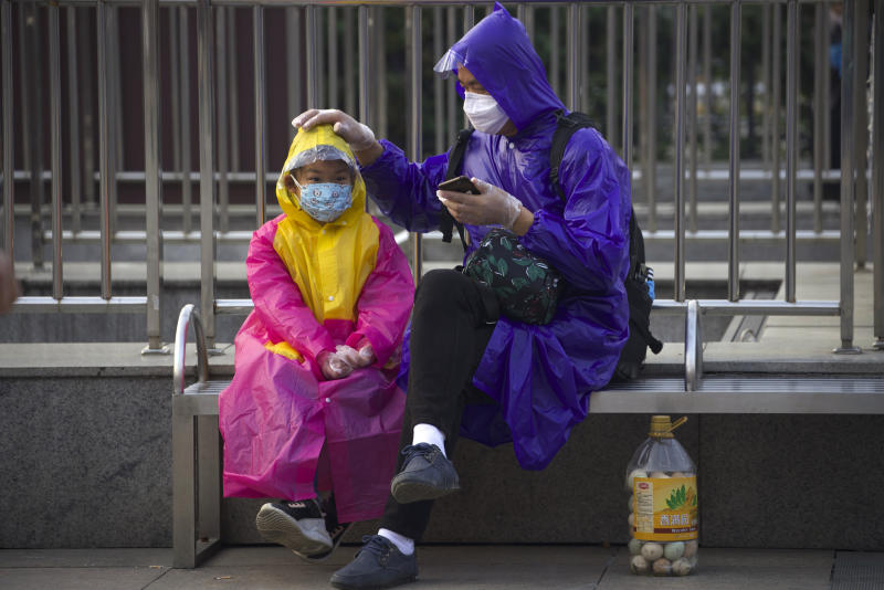 Passengers wearing face masks and raincoats to protect against the spread of new coronavirus sit outside of Hankou train station after of the resumption of train services in Wuhan in central China's Hubei Province, Wednesday, April 8, 2020. After 11 weeks of lockdown, the first train departed Wednesday morning from a re-opened Wuhan, the origin point for the coronavirus pandemic, as residents once again were allowed to travel in and out of the sprawling central Chinese city. (AP Photo/Ng Han Guan)