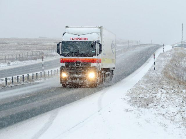 A lorry makes its way through the snow on the A66 in Cumbria (Owen Humphreys/PA)