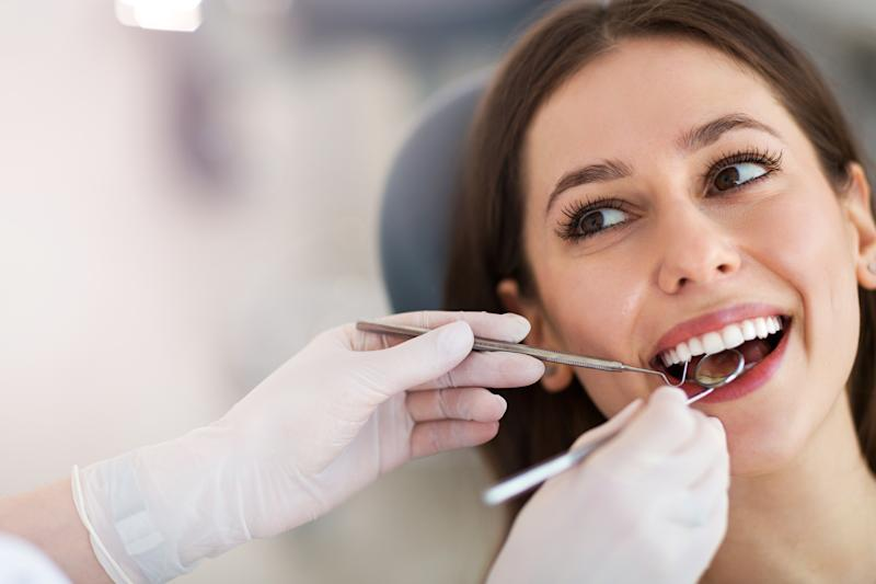 Woman having teeth examined at dentists