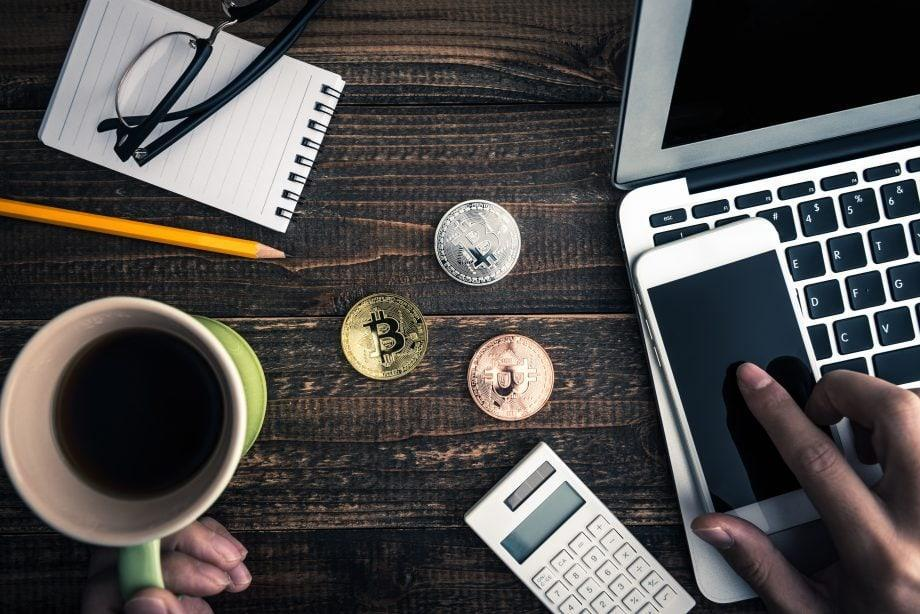 bitcoin and computer on wooden table