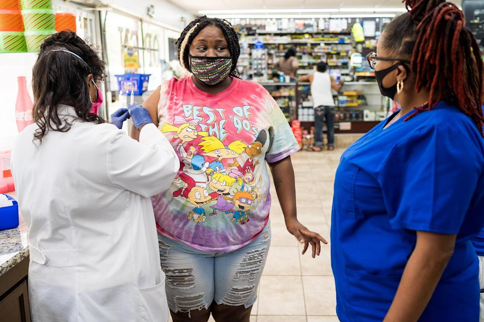 Dejah Crawford, 21, chats with nurse Andretta Griffin as Dr. Karen Smith prepares to administer her Covid-19 vaccination at the J&L Grocery convenience store in Raeford, N.C. (Justin Kase Conder / for NBC News)