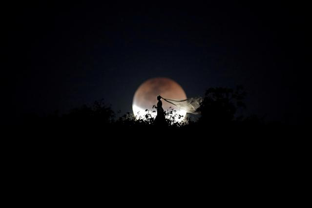 <p>A bride poses for photo during a total lunar eclipse from in Brasilia, Brazil, July 27, 2018. (Photo: Ueslei Marcelino/Reuters) </p>