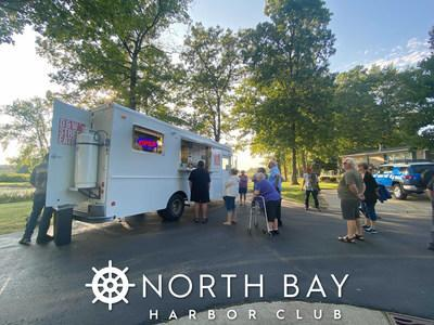 Residents and other attendees, at the North Bay Harbor Club ribbon cutting ceremony, enjoy complementary food by local establishments.