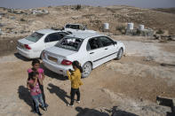 Girls play around smashed vehicles following a settlers' attack from nearby settlement outposts on the Palestinian Bedouin community, in the West Bank village of al-Mufagara, near Hebron, Thursday, Sept. 30, 2021. An Israeli settler attack last week damaged much of the village's fragile infrastructure. (AP Photo/Nasser Nasser)