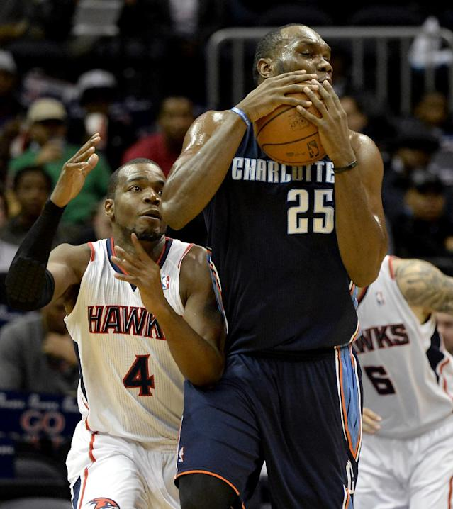 Charlotte Bobcats center Al Jefferson (25) grabs the rebound in front of Atlanta Hawks' Paul Millsap (4) and Pero Antic (6) in the first half of their NBA basketball game on Saturday, Dec. 28, 2013, in Atlanta. (AP Photo/David Tulis)