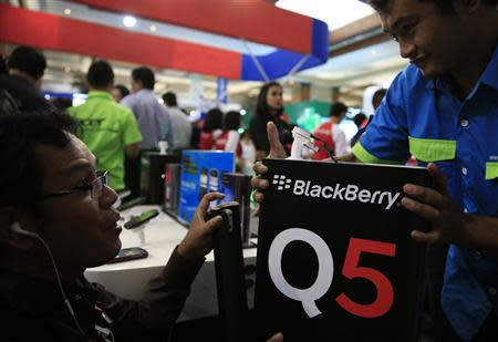 A worker prepares a Blackberry display during Digital Imaging Expo in Jakarta March 5, 2014. REUTERS/Beawiharta