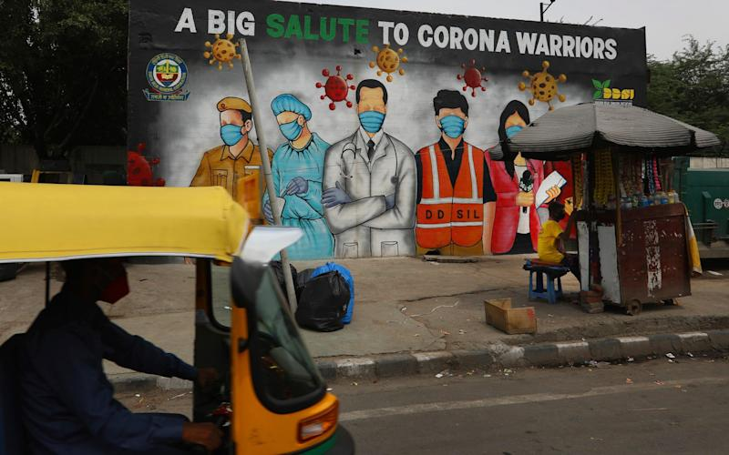 An autorickshaw drives past a graffiti thanking frontline workers in the fight against the coronavirus, in New Delhi, India - Manish Swarup /AP