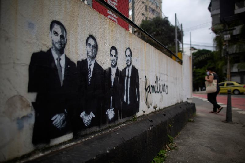 A woman walks near a wall depicting Brazilian President Jair Bolsonaro (2-L) and his sons, congressman Eduardo Bolsonaro (L), Senator Flavio Bolsonaro (1-R) and councilman Carlos Bolsonaro (2-R) and reading Familitia -combination of the words family and militia- at the Grajau neighbourhood in Rio de Janeiro, Brazil, on May 14, 20120, amid the new coronavirus pandemic. (Photo by MAURO PIMENTEL / AFP) (Photo by MAURO PIMENTEL/AFP via Getty Images)