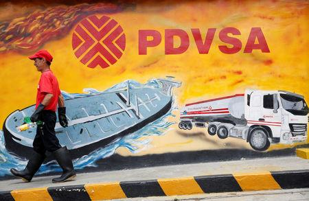 FILE PHOTO: A worker walks past a mural with a PDVSA logo at its gas station in Caracas, Venezuela August 29, 2014. REUTERS/Carlos Garcia Rawlins/File Photo