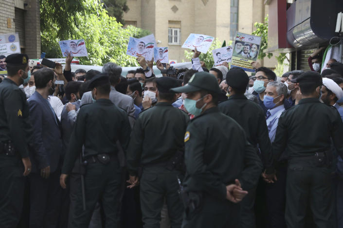 Supporters of former President Mahmoud Ahmadinejad hold his posters while he entered at Interior Ministry to register his name as a candidate for the June 18 presidential elections, as police officers prevent them to approach the ministry building in Tehran, Iran, Wednesday, May 12, 2021. The country's former firebrand president will run again for office in upcoming elections in June. The Holocaust-denying Ahmadinejad has previously been banned from running for the presidency by Supreme Leader Ayatollah Ali Khamenei in 2017, although then, he registered anyway. (AP Photo/Vahid Salemi)