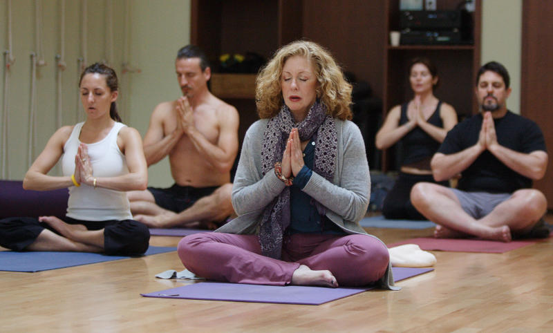 Joan Barnes (C), owner of Yoga Studio, takes a yoga class at her studio in San Francisco, California, in this March 29, 2006 file photo. Americans spend some $2.95 billion a year on yoga classes, equipment, clothing, vacations, videos and more, according to a study commissioned by monthly magazine Yoga Journal, fueled in part by aging baby boomers seeking less aggressive ways to stay fit. Roughly 16.5 million people were practicing yoga in the United States early last year, either in studios, gyms or at home, up 43 percent from 2002, the study found. To accompany feature Leisure Yoga. REUTERS/Kimberly White/Files