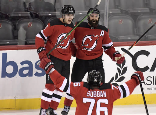 New Jersey Devils center Yegor Sharangovich (17) celebrates his game-winning overtime goal with right wing Kyle Palmieri (21) and defenseman P.K. Subban (76) as the Devils defeated the Boston Bruins 2-1 in an NHL hockey game Saturday, Jan. 16, 2021, in Newark, N.J. (AP Photo/Bill Kostroun)