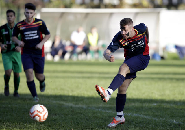 A Desio player, his face painted with black marks as a symbolic sign against racism, kicks the ball during a youth team soccer match between Desio and Sovicese at the municipal stadium in Desio, near Milan, Italy, Saturday, Nov. 9, 2019. The initiative comes a week after a 10-year-old member of the Aurora Desio team was allegedly subjected to racist abuse during a match. (AP Photo/Luca Bruno)