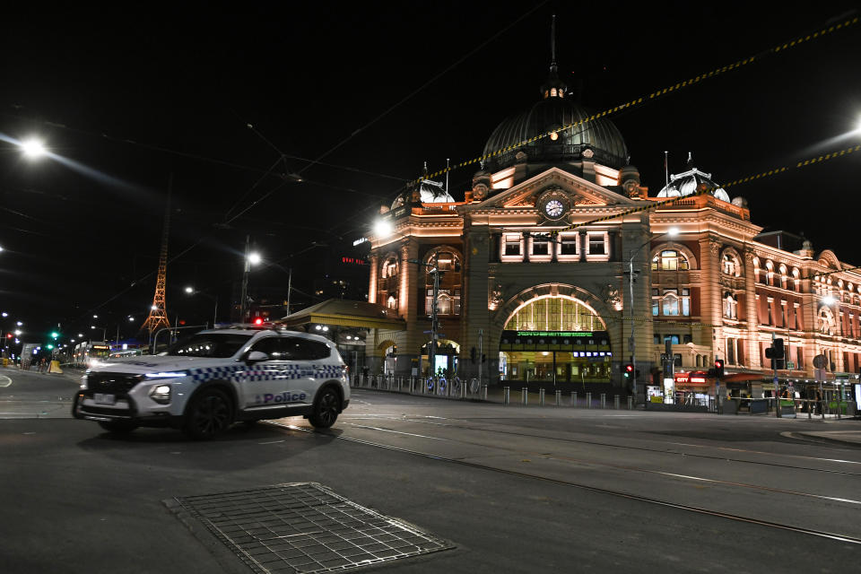 A police car is seen outside Flinders Street Station after the citywide curfew was put into place for the first time. Source: AAP