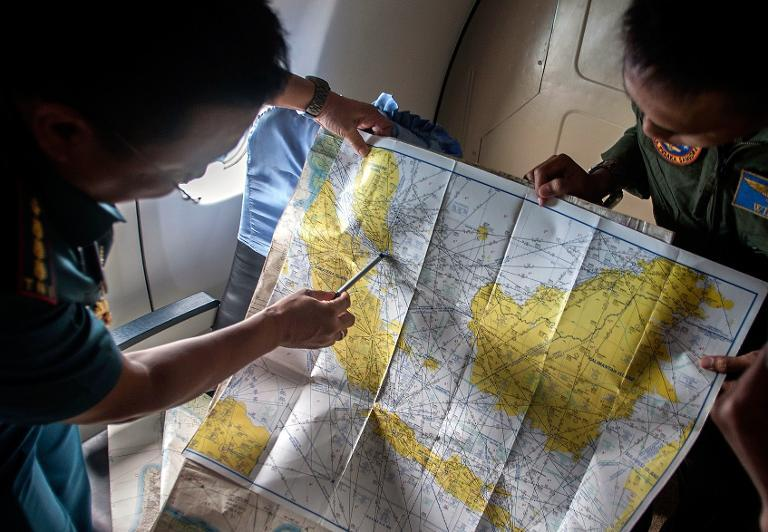 Indonesian army personnel read a map during a search and rescue (SAR) operation for missing Malaysian air carrier AirAsia flight QZ8501, over the waters of the Java Sea on December 29, 2014