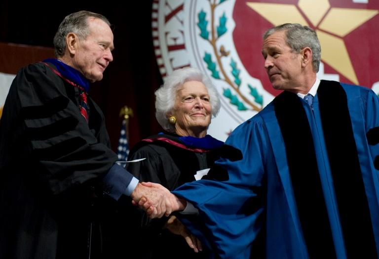 In this file photo taken on December 11, 2008 US President George W. Bush (R) shakes hands with his father, former President George H.W. Bush (L) before his mother, former First Lady Barbara Bush (C), after delivering the commencement address during the Texas A&M University graduation ceremony