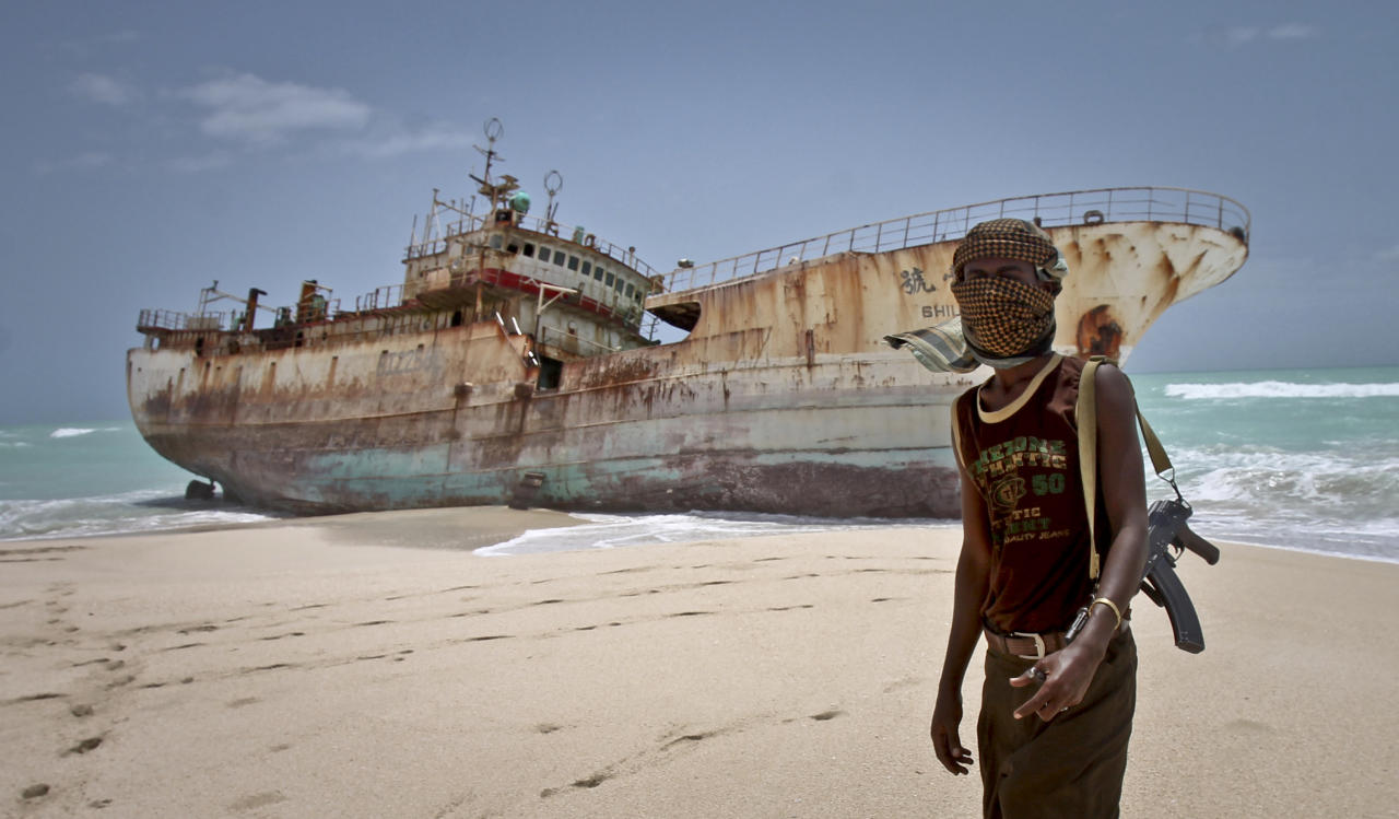 In this photo taken Sunday, Sept. 23, 2012, masked Somali pirate Abdi Ali stands near a Taiwanese fishing vessel that washed up on shore after the pirates were paid a ransom and released the crew, in the once-bustling pirate den of Hobyo, Somalia. The empty whisky bottles and overturned, sand-filled skiffs that litter this shoreline are signs that the heyday of Somali piracy may be over - most of the prostitutes are gone, the luxury cars repossessed, and pirates talk more about catching lobsters than seizing cargo ships. (AP Photo/Farah Abdi Warsameh)